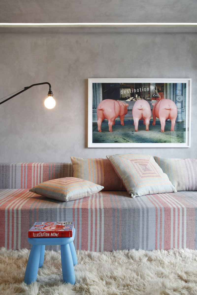 sala-de-estar-com-banqueta-azul-sofa-listrado-e-arte-pastel-Studio Guilherme Torres
