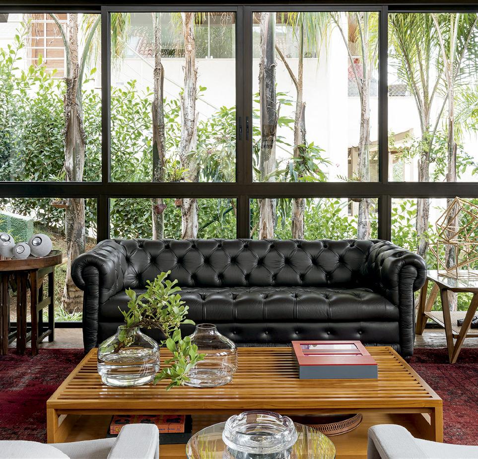 O sofá Chesterfeld e a mesa de centro Vila Nova, assinada por Paulo Alves, dominam a sala de estar.