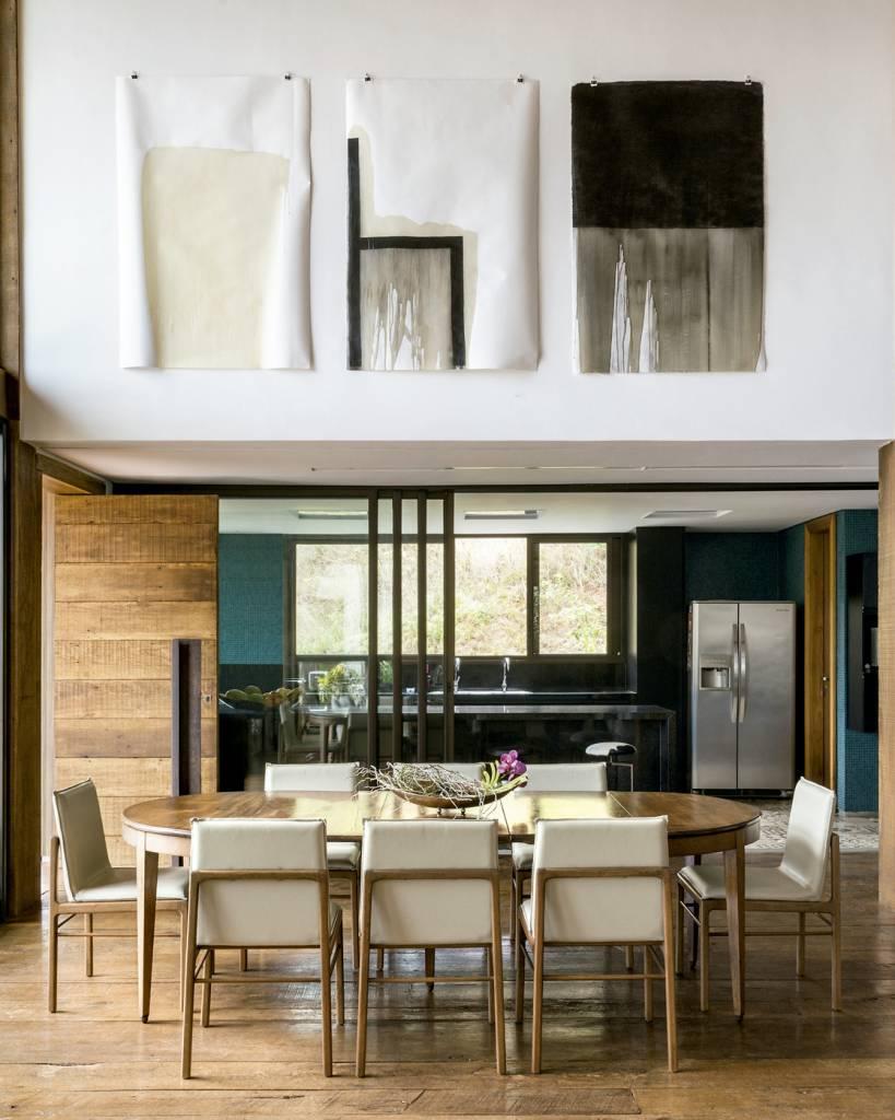 Isolada da cozinha por uma porta de vidro, a sala de jantar traz mesa dos anos 1950, do acervo da família da moradora, aliada a cadeiras ADA, do Estudiobola. As telas são criação do filho Bruno.