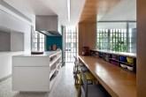 Cozinha com piso claro, bancada de madeira e bemiluminada