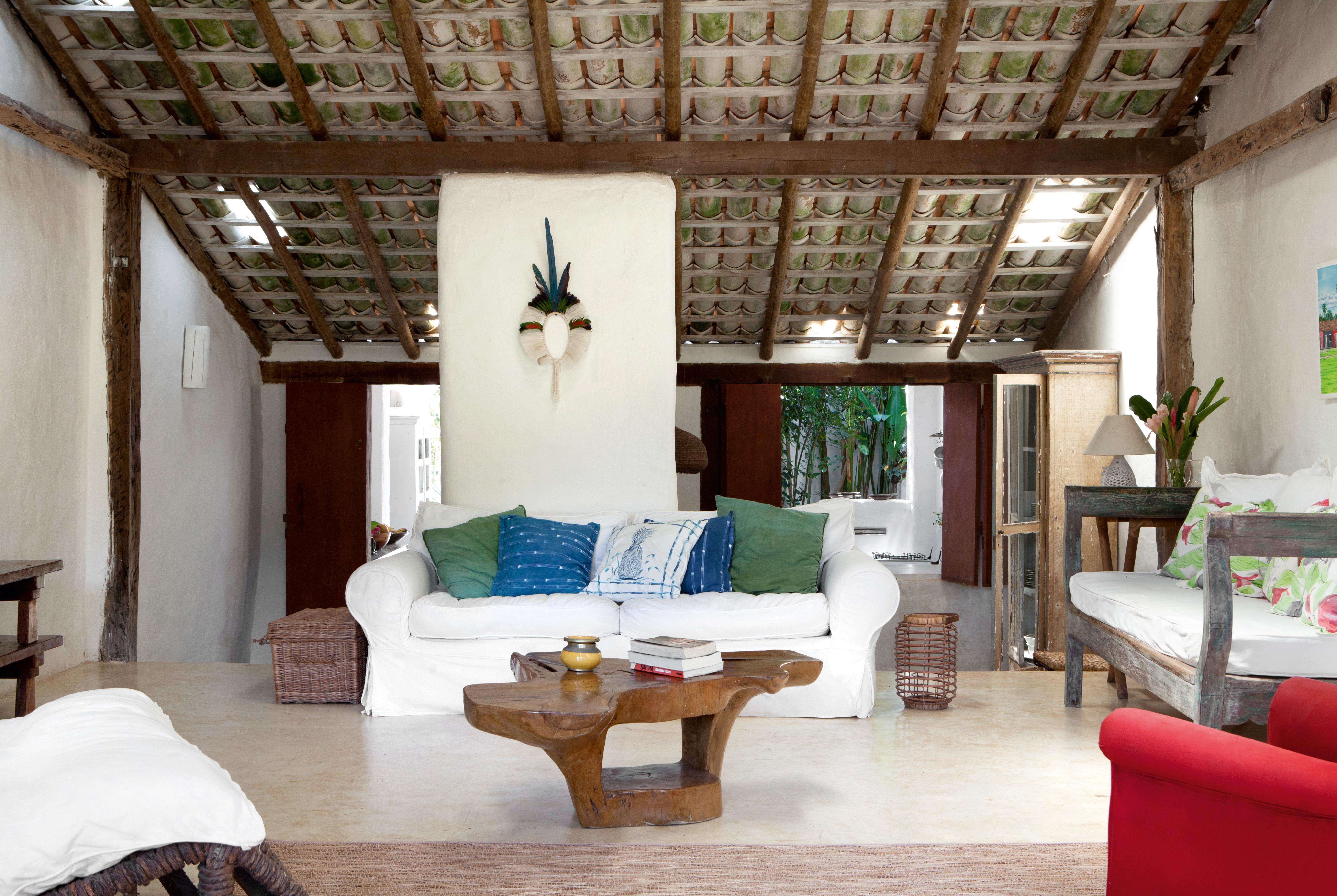 A sala de estar tem poucos móveis e permite a livre circulação. Destaque para a mesa orgânica de Hugo França, para o cocar feito por Aruê (um índio pataxó da região) e para as telhas à vista.