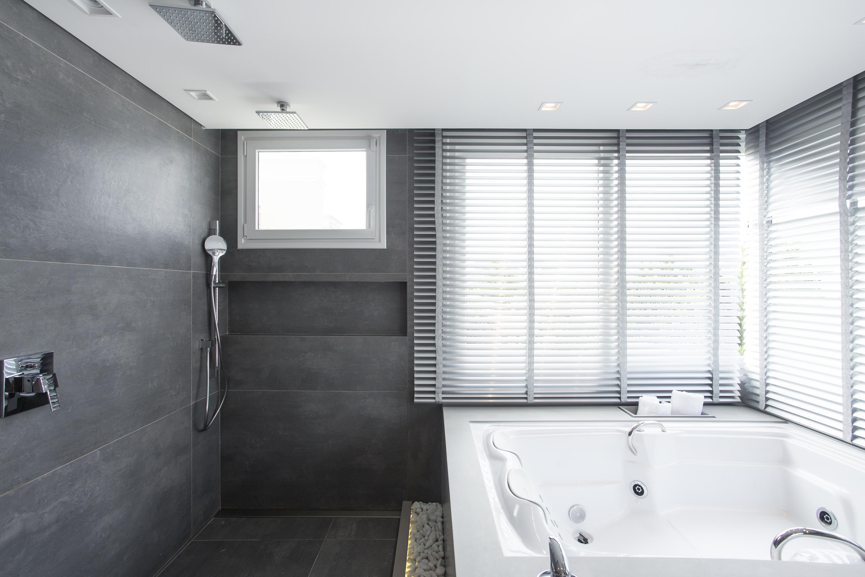Banheiro com banheira e parede cinza