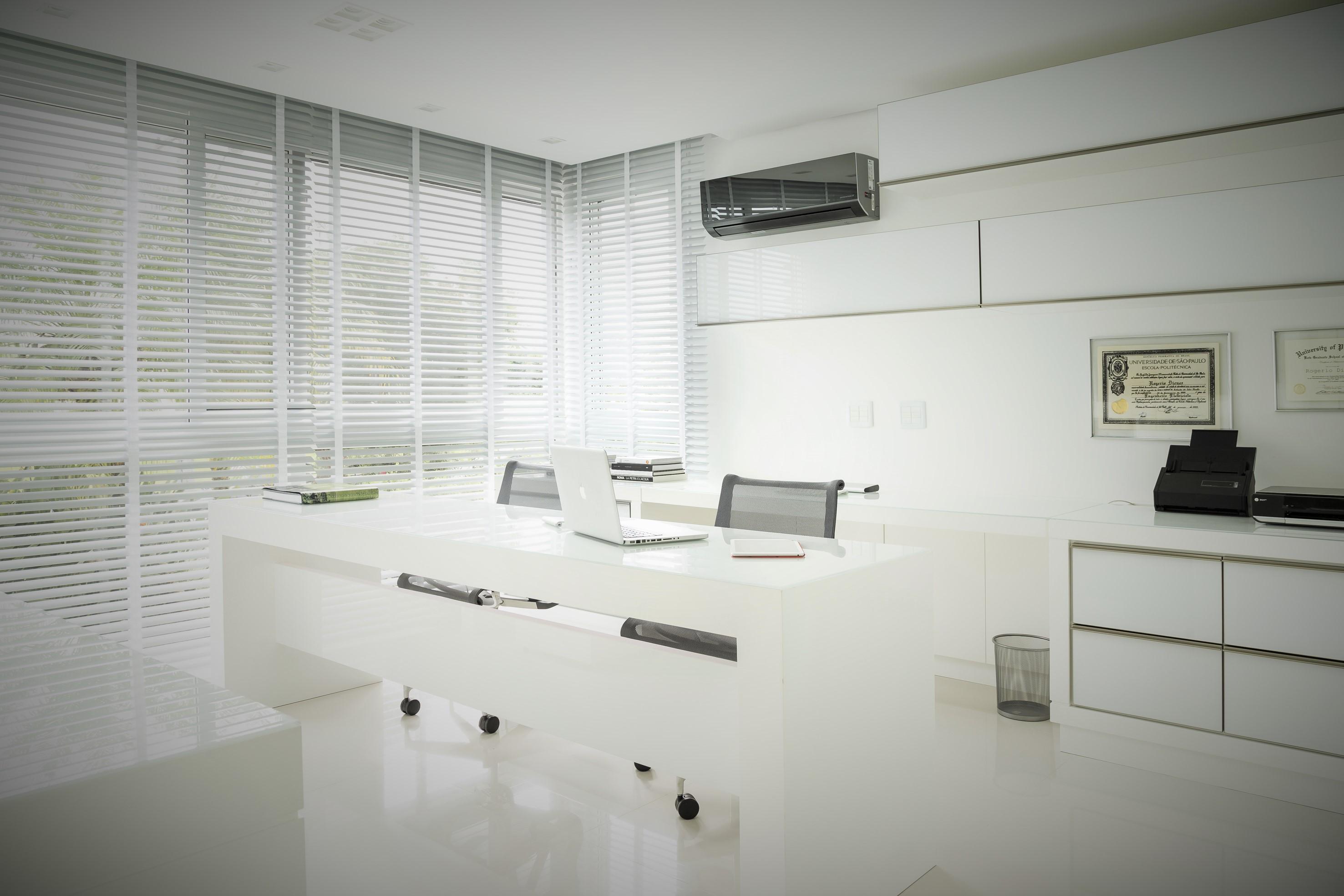 Escritório com móveis de linhas simples e com branca predominante