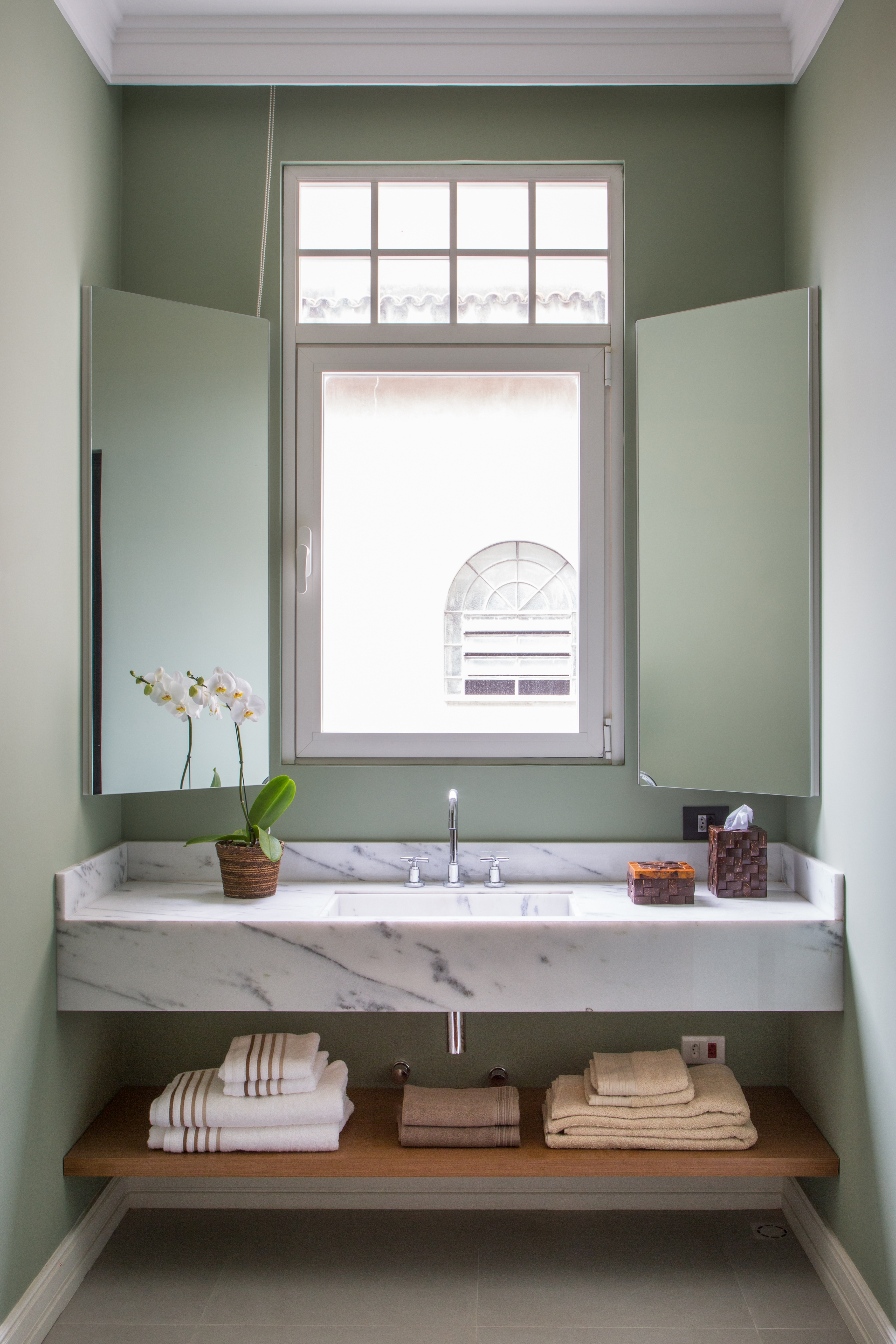 Banheiro com paredes verdes e bancada de mármore