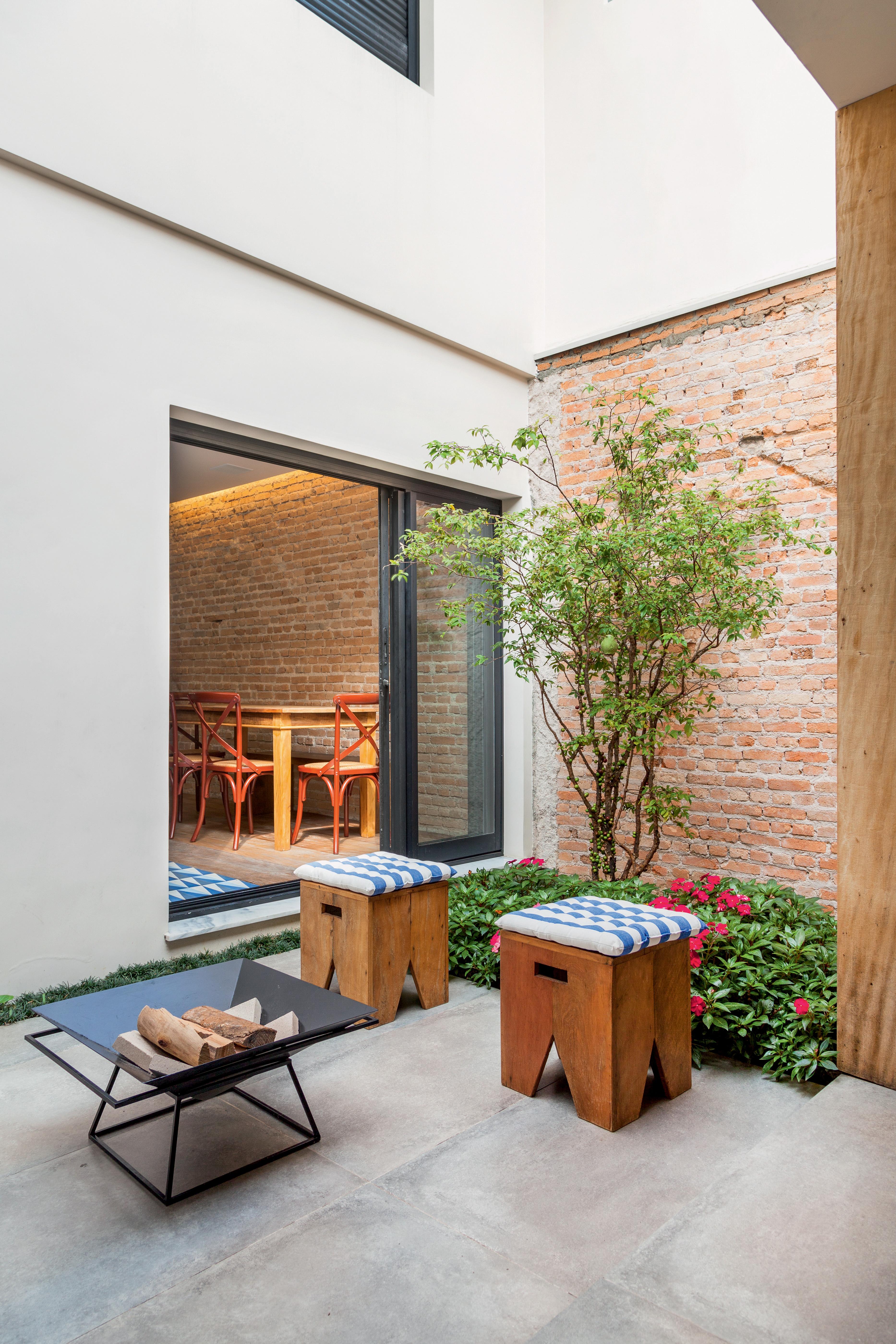 Lareira portátil e banquinhos em pàtio de 13 m², com projeto das arquitetas Sarah Bonanno de Almeida e Marina Cardoso de Almeida, do escritório Tria Arquitetura.