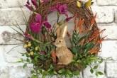 Guirlanda de páscoa de galhos secos, com flores roxas e laranjas e um coelho