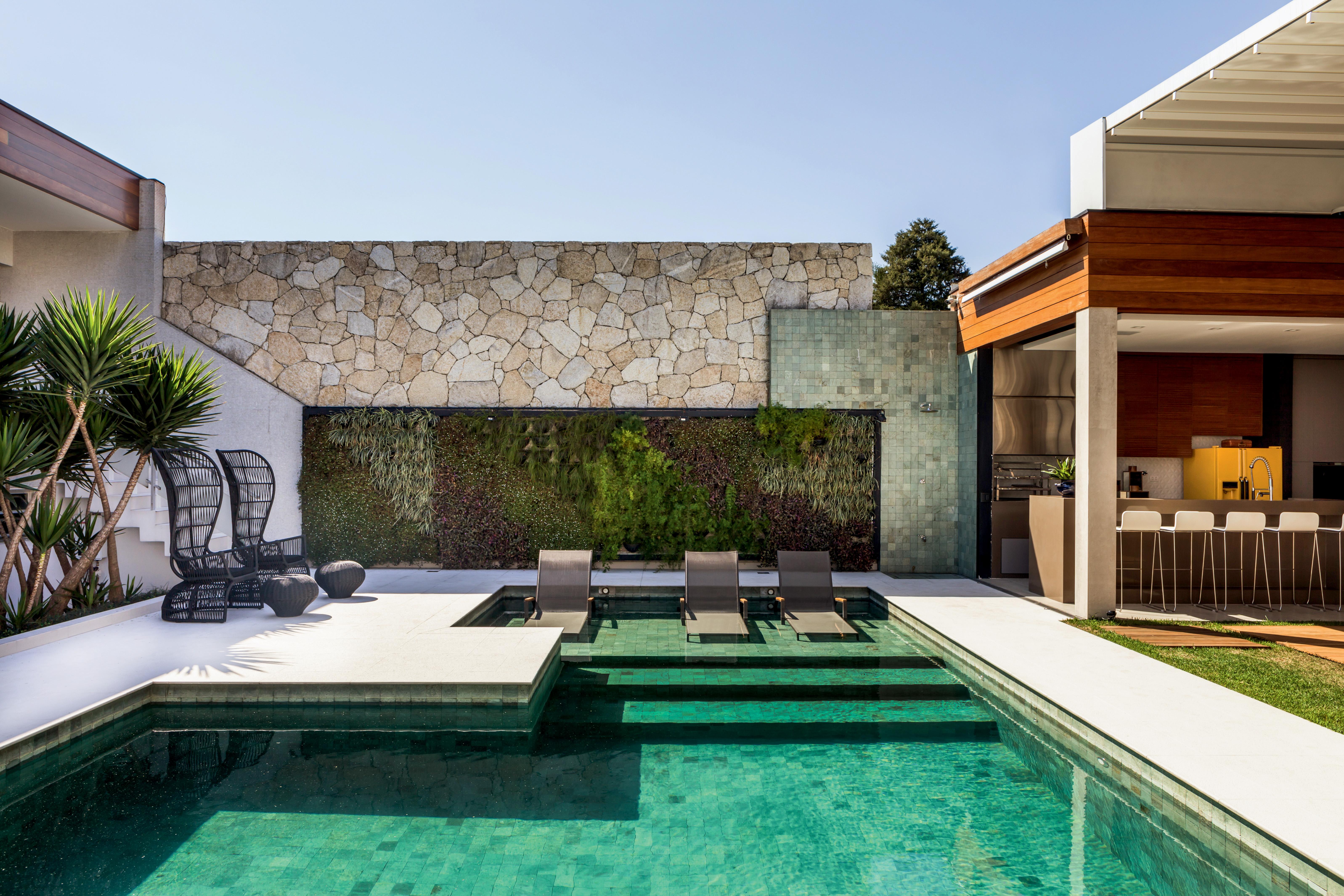 Jardim vertical e piscina com revestimento da pedra verde hijauem projeto dos arquitetos Gil Cioni e Olegário de Sá