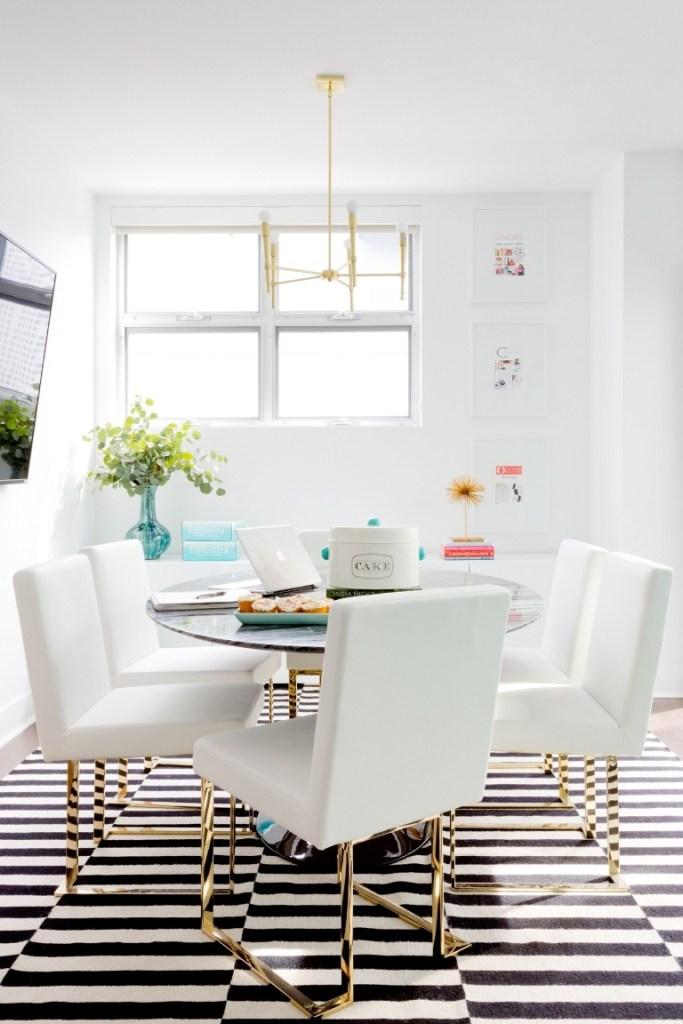 Escritório com cadeiras brancas e tapete listrado branco e preto