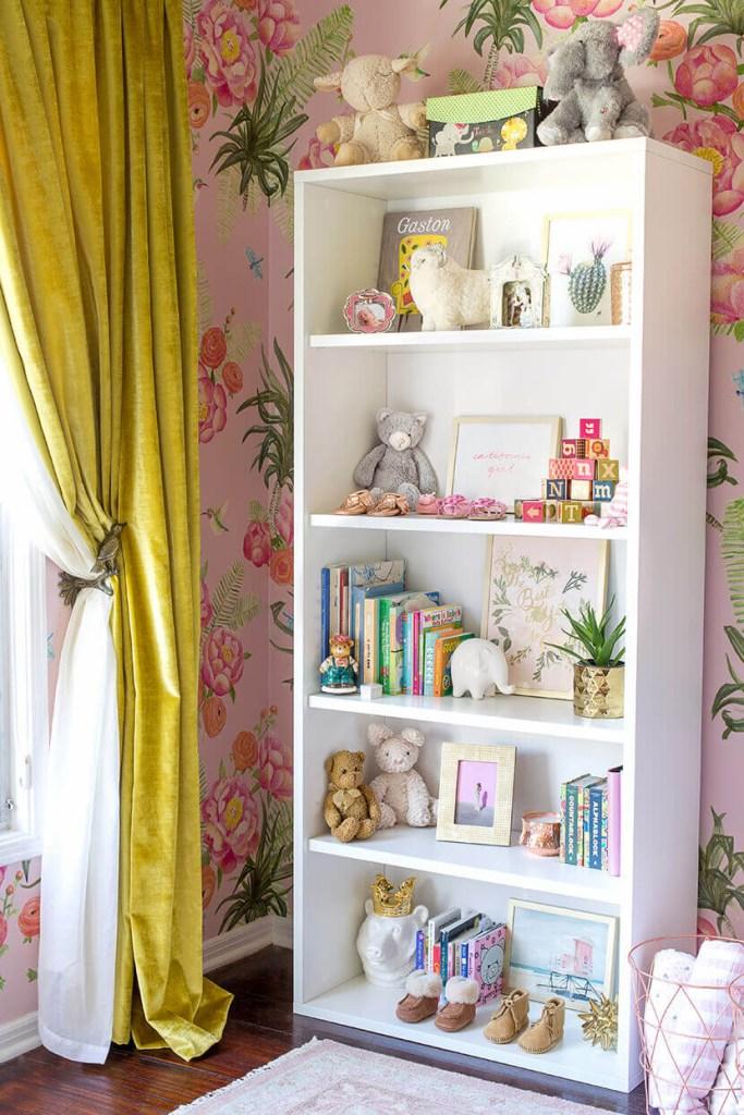 Quarto feminino de bebê com paredes rosa floridas