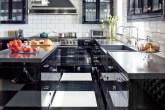 Cozinha em preto e branco com mesa de janta com canto alemão