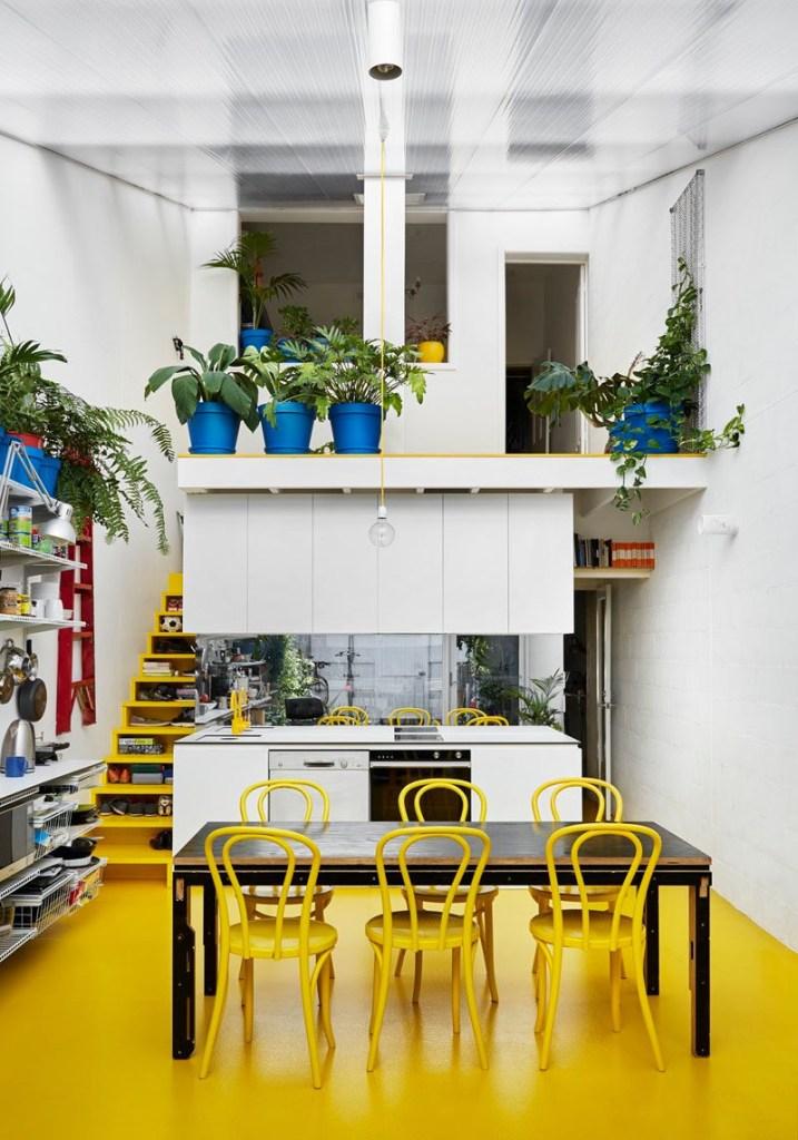 Escada aberta amarela que funciona como prateleira
