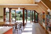 Sala de jantar integrada a biblioteca de madeira