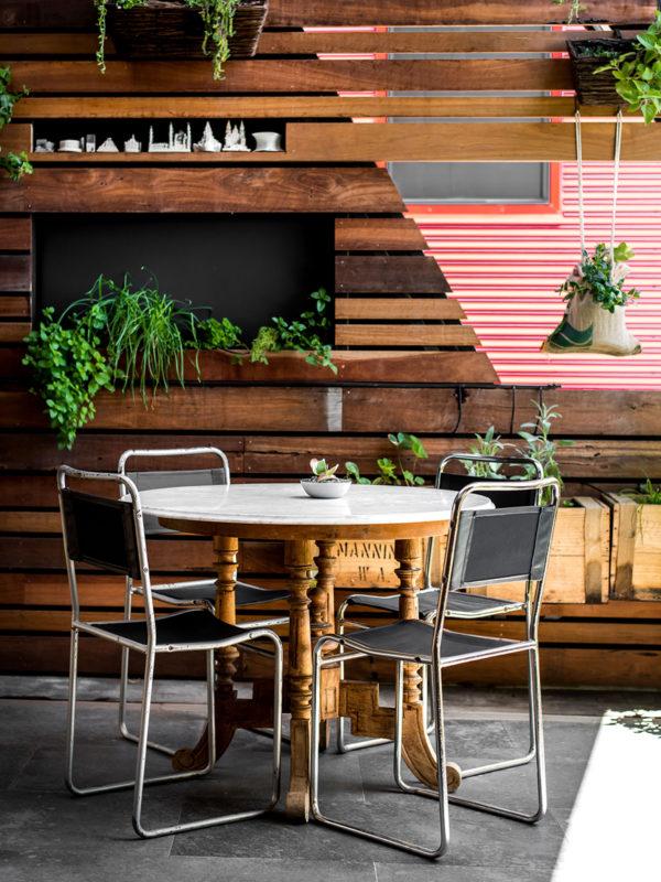 Área externa pequena com vasos nas paredes de madeira
