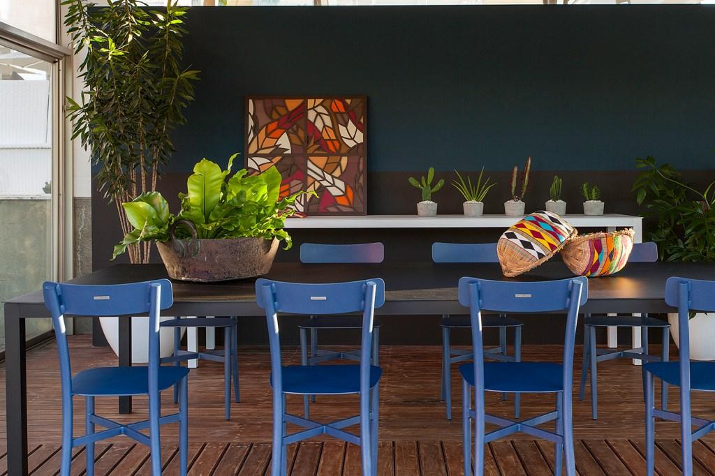 Sala de estar e de jantar integradas com parede preta e azul