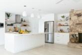 Cozinha branca com ilha, estilo escandinavo e acabamento em madeira e pedra