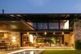 Casa com piscina, móveis de madeira e área social integrada ao jardim
