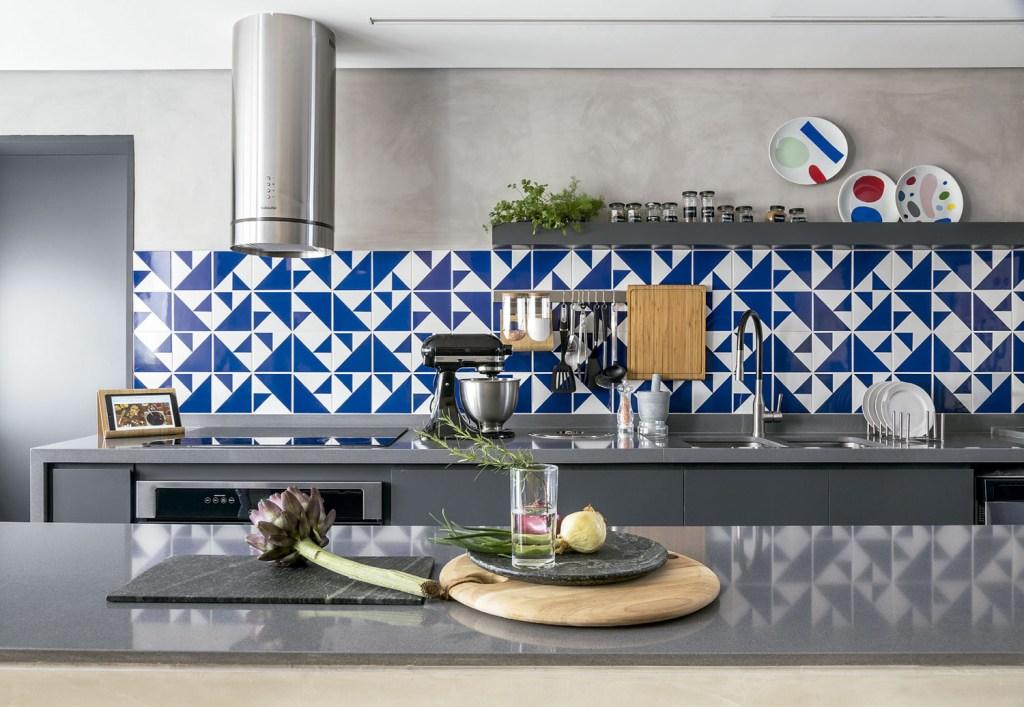 O azul e o branco do painel casam direitinho com o pínus dos armários e com o cinza utilizado no piso, nas paredes e nas bancadas de composto sintético.