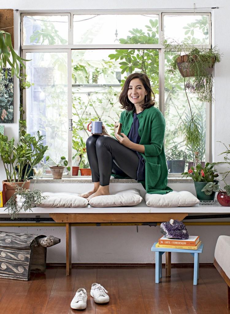Nana na janela que dá para o quintal do apartamento térreo, repleto de plantas (são mais de 100 espécies). Sempre que pode, ela também se dedica a fazer pães de fermentação natural.