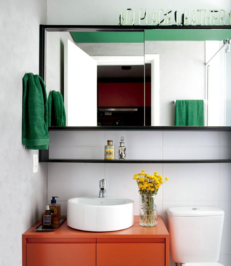 Com décor colorido e pegada industrial, este apartamento inteiro é menor do que o living de muita gente. Atrás do espelho do banheiro, há lugar para objetos.