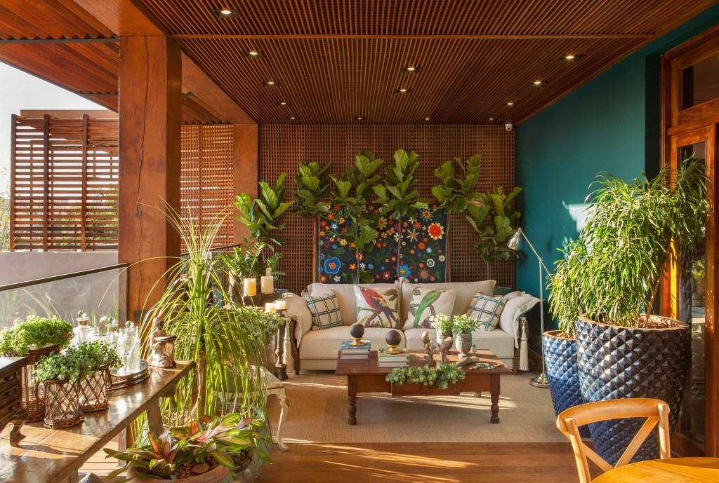 Varanda com teto e paredes de muxarabi exalta a natureza