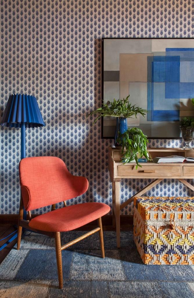 Living com papel de parede de abacaxis e poltrona laranja