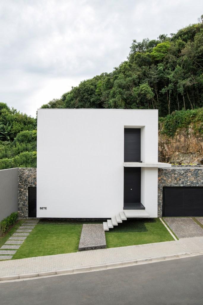 Uma casa compacta, com volume puro e grandes vãos envidraçados que integrassem o entorno foram os pedidos do morador desta casa, em Pilarzinho, Curitiba