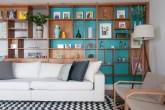 Área social tem décor colorido e estante divisória