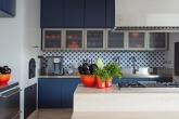 Cozinha com décor azul e ladrilho hidráulico usado como tapete