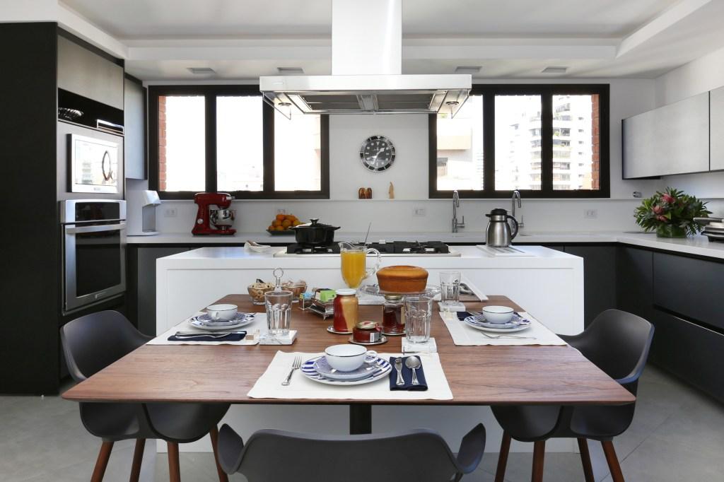 Cozinha com ilha central e mesa de jantar em área integrada