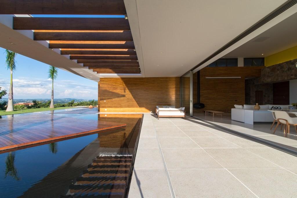 Living amplo integrado ao deque com piscina