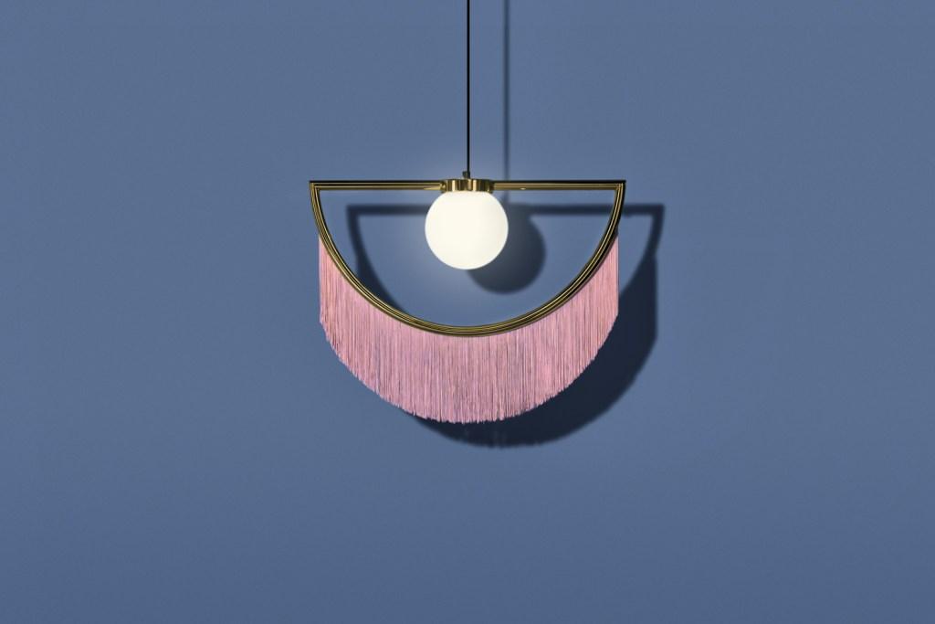 Em dourado e com franjas em tom rosado, a peça Wink tem design tipo pêndulo e conta com uma cúpula redonda central