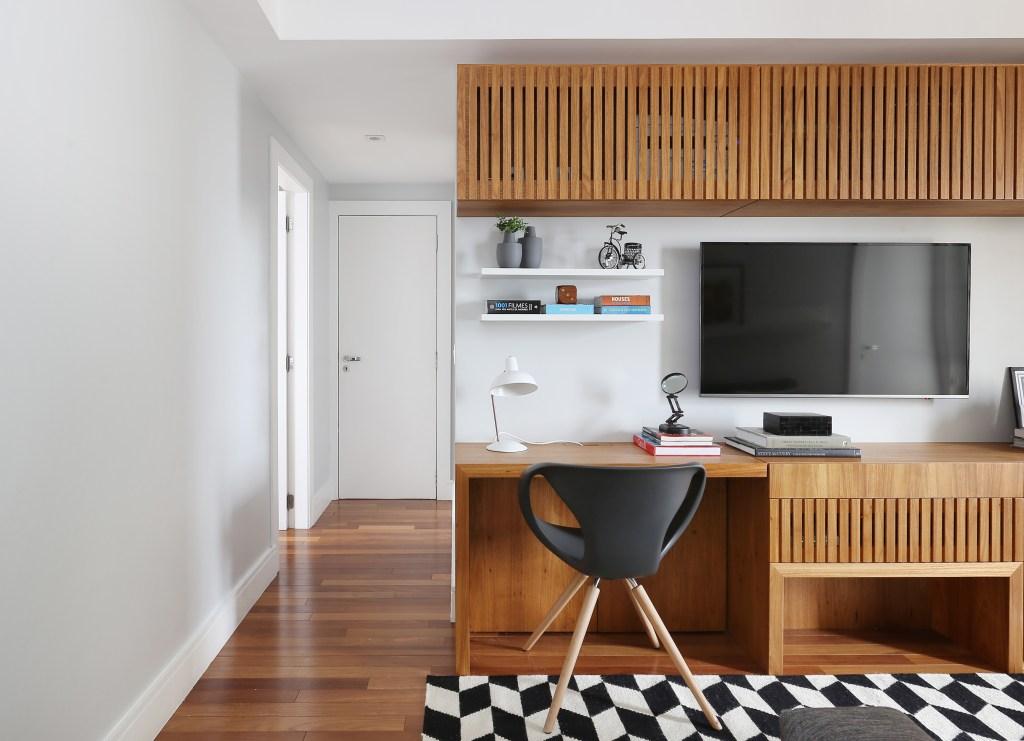 Sala de TV com home office em ambiente organizado
