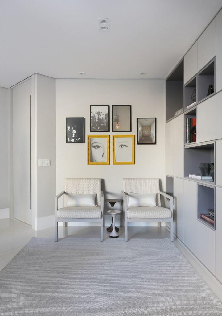 Área social com estante contínua e espelho para dar amplitude visual