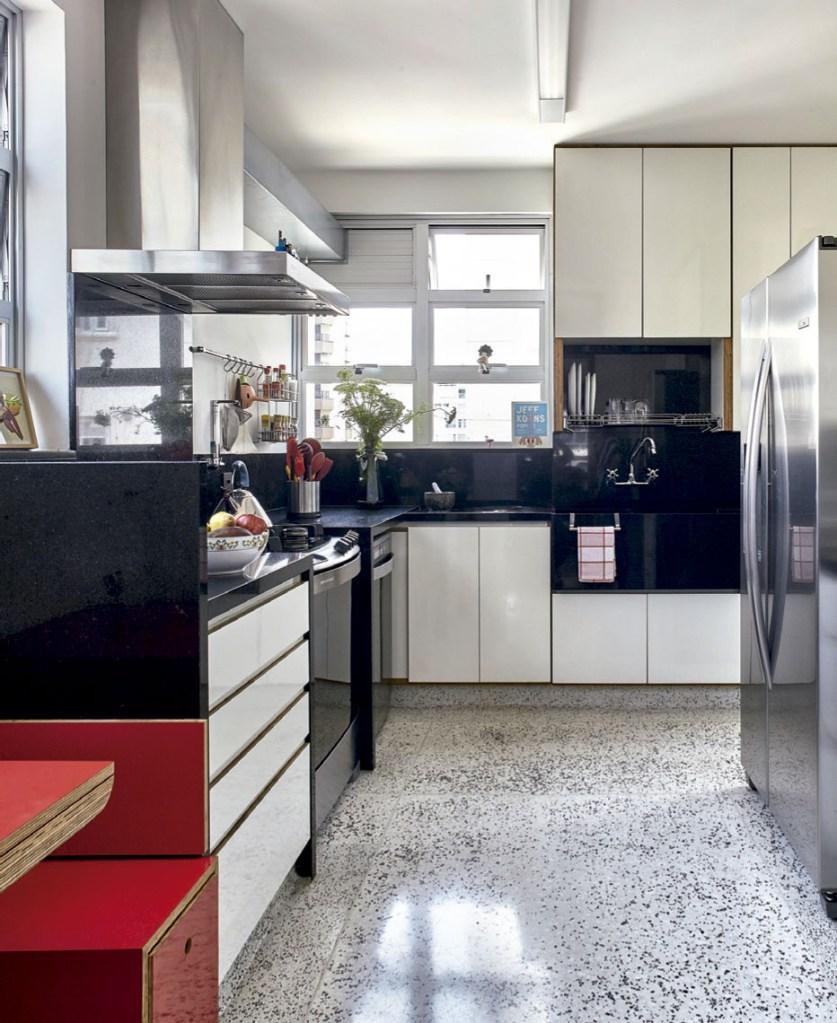 A cozinha combina piso de granilite com copa de compensado naval vermelho.