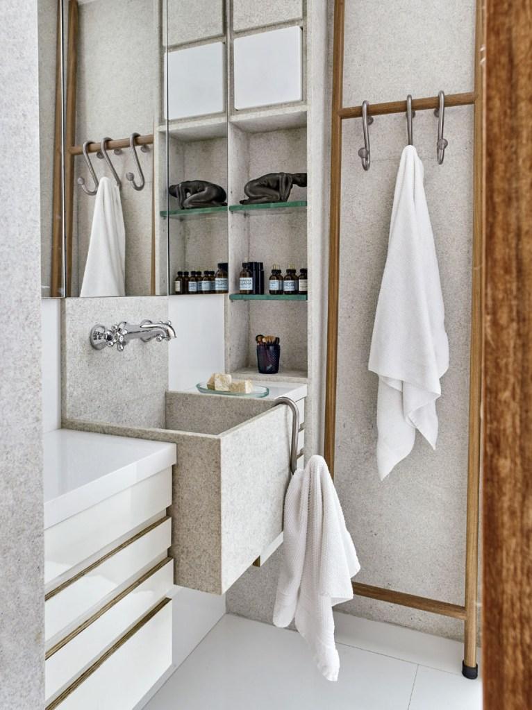 Ganchos de açougueiro viraram porta-toalhas no banheiro. Pedaços de mangueira de PVC transparente protegem as pontas.
