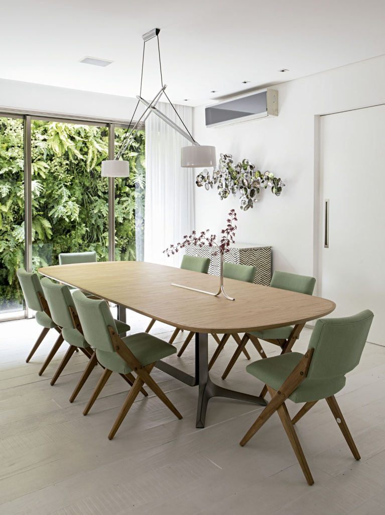 O muro verde do jardim (Maha Paisagismo) se estende até a porta da sala de jantar. Lustre da Fas Iluminação, mesa de Jader Almeida (Micasa), cadeiras de jantar da Dpot, vaso de Guilherme Wentz e escultura de Jonathan Adler.