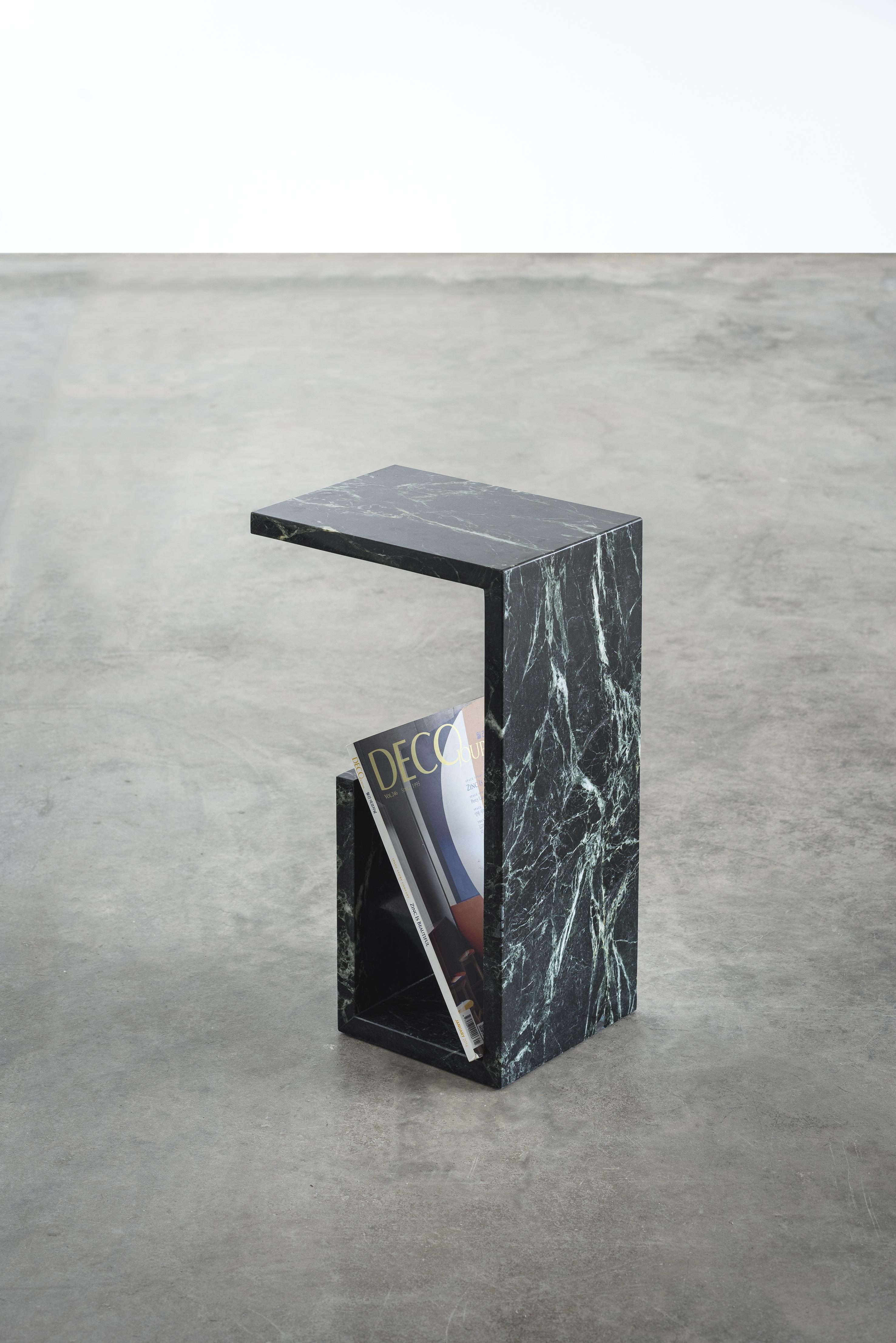 A mesa-revisteiro feita com mármore verde tikal é inspirada na linguagem arquitetônica