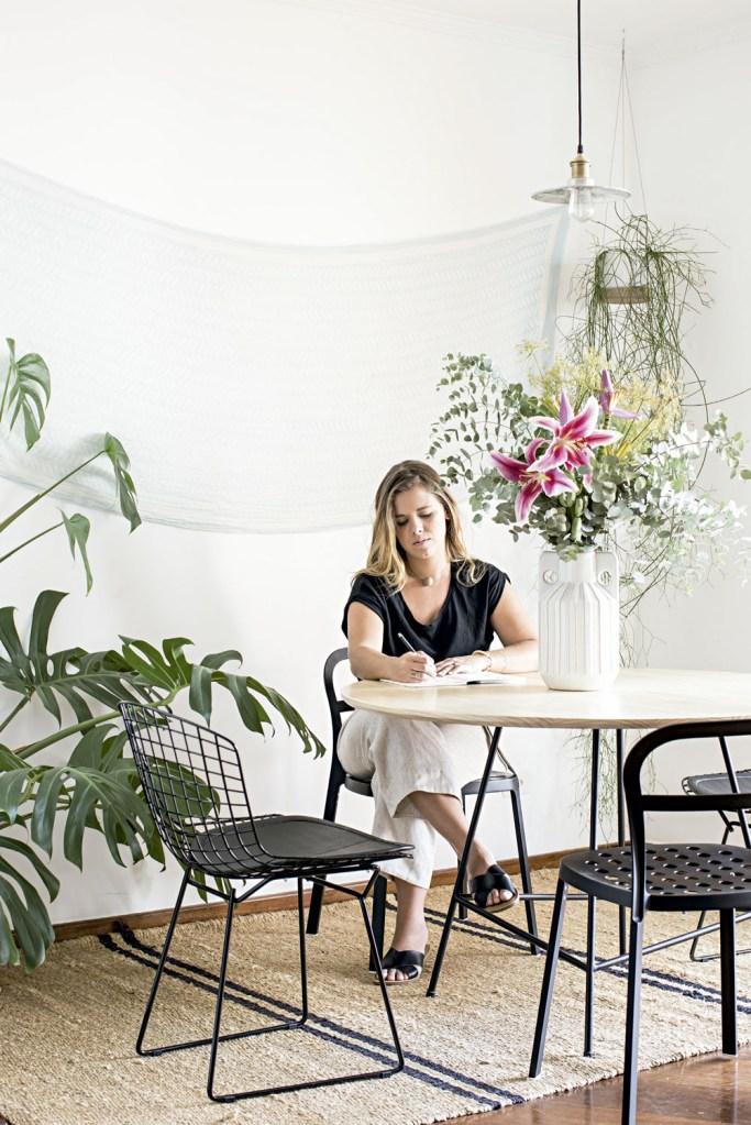 Cadeira Bertoia, da Tok & Stok, e mesa da Marcenaria Marcenetto. À esquerda, costela-de-adão e arranjo com lírios, eucalipto e for de bananeira. Vasos de cerâmica da Amapá Flowershop.