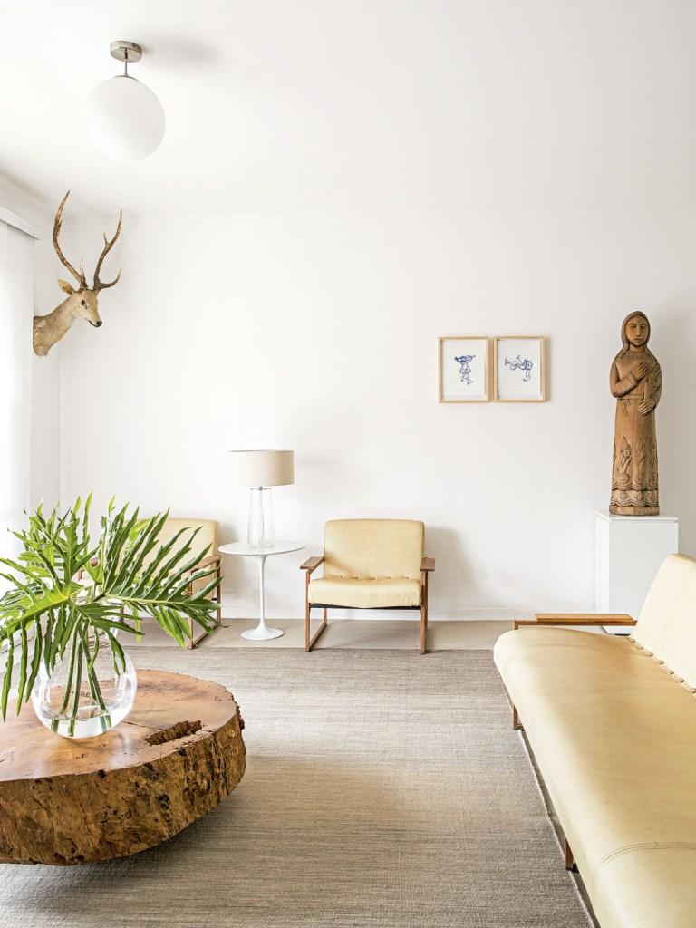 Em primeiro plano, sofá de Jorge Zalszupin e, ao fundo, obras de Armarinhos Teixeira e escultura de Santo Expedito garimpada na feira do Bixiga.