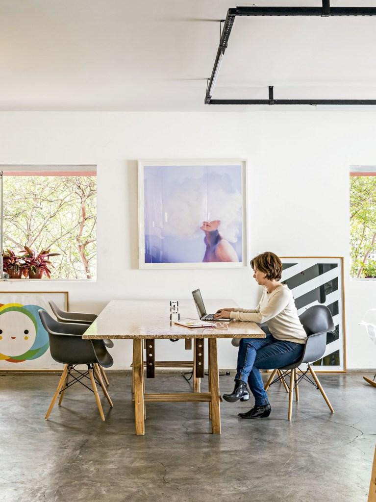 Juliane numa das mesas de trabalho. Na parede, aparece a fotografa Nuvem, de César Cury.