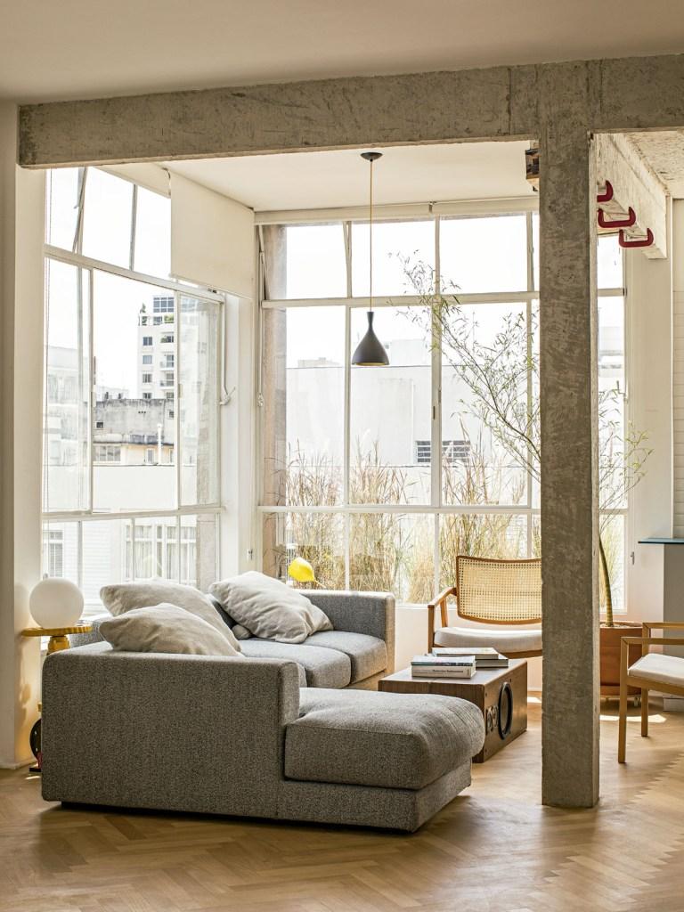 O sofá herdado da irmã do morador veio do Rio de Janeiro e ganhou lugar privilegiado ao lado da janela, onde há uma jardineira com capim-do-texas.