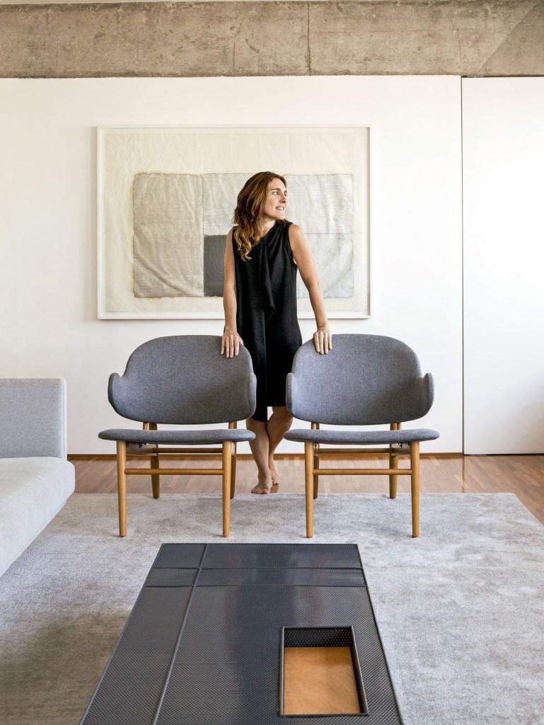 Natalia entre as poltronas da Artesian e diante do quadro do artista SergioSister. As cores da obra influenciaram a paleta do espaço.