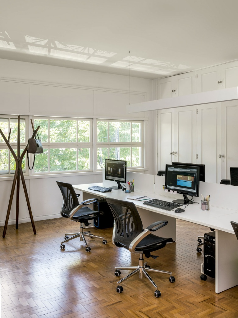 A estrutura original, com janelões e piso de tacos, permaneceu intacta. Com isso, as equipes trabalham em ambientes que não parecem escritórios convencionais.