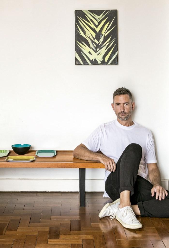 Ricardo ao lado de um banco de madeira e de uma tela do venezuelano Jaime Gili.