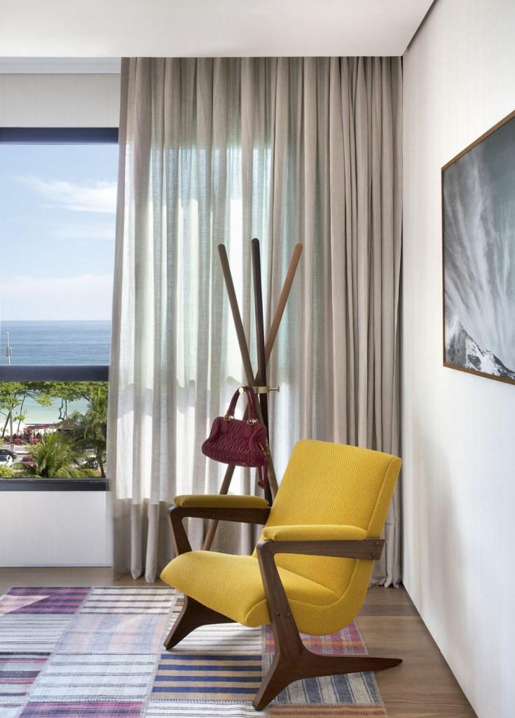 Emoldurada na janela, a praia traz um motivo extra para curtir este apartamento, que privilegia tons neutros e design nacional
