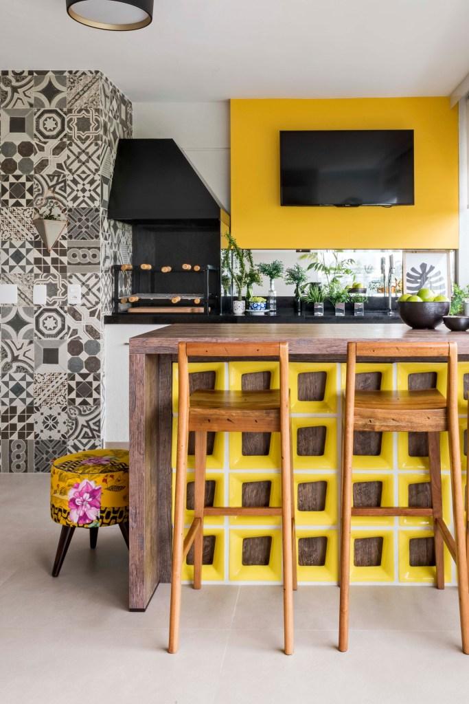 Varanda com cobogós amarelos na bancada e painel de TV amarelo