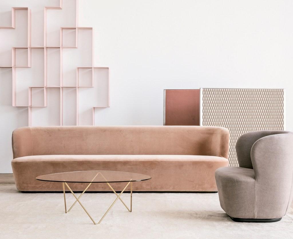 Sofá de veludo rosa claro, poltrona cinza e mesa de vidro de centro