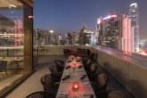 rooftop com mesas e cadeiras e luzes vermelhas