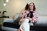 Nina Yashar sentada em um sofá cinza