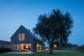 Exterior da casa com as luzes internas acesas ao anoitecer e uma árvore ao lado